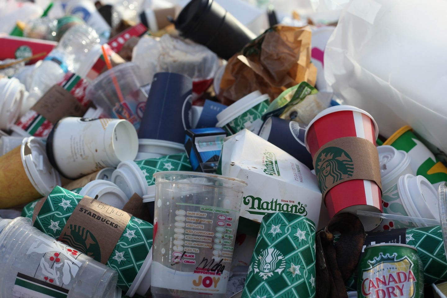Empty cups, both plastic and paper, take out containers, straws, and other trash sit in a multi-colored pile. Starbucks, Nathans, Dunkin Donuts, and Canada Dry logos are visible on some of the items.