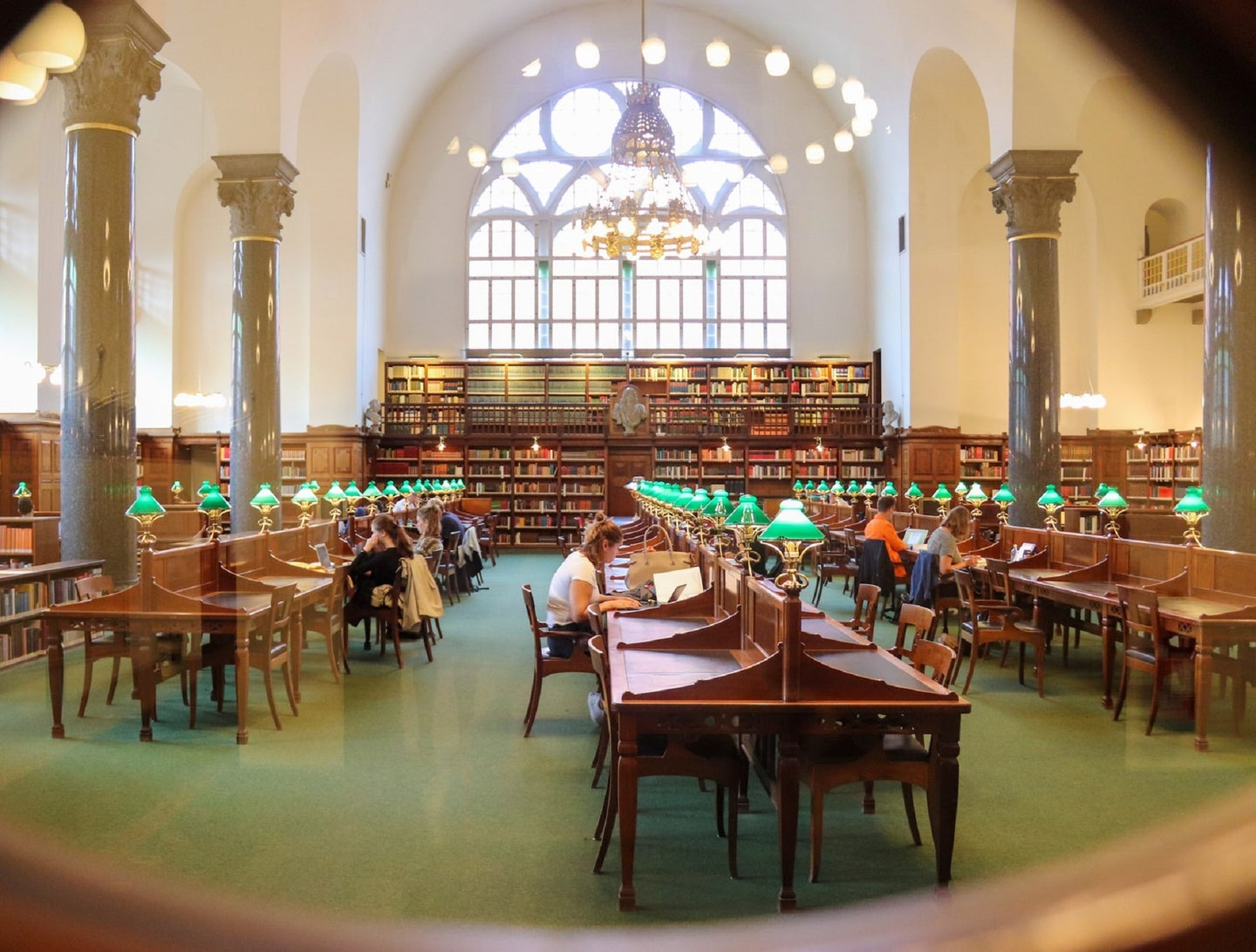 College library with students at tables and green lamps