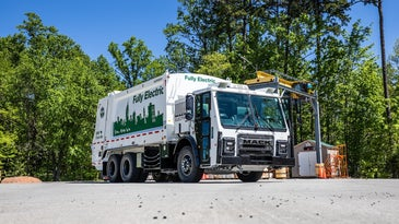 an electric garbage truck in a parking lot