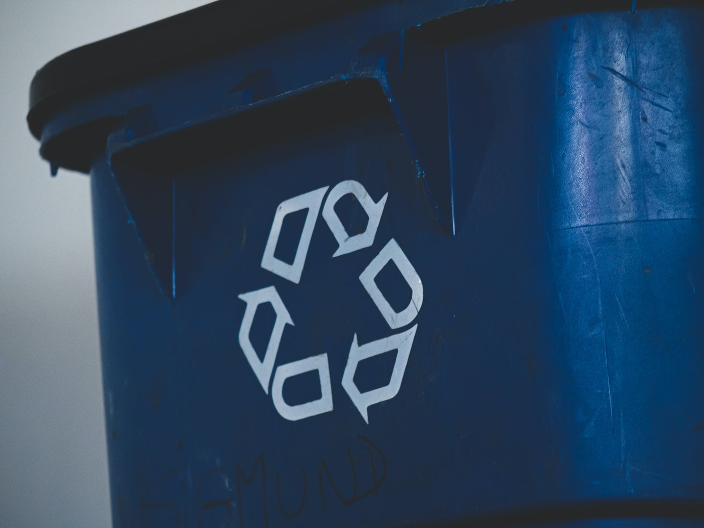 A blue recycling bin with a recycling symbol on it.
