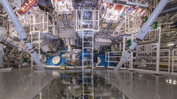 A science lab with a nuclear fusion reactor in the background, and a ladder leading to the center.