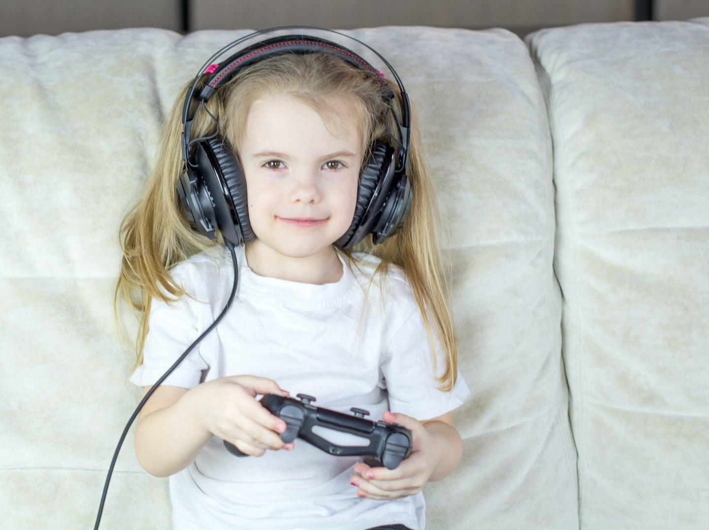 A child with headphones playing video games