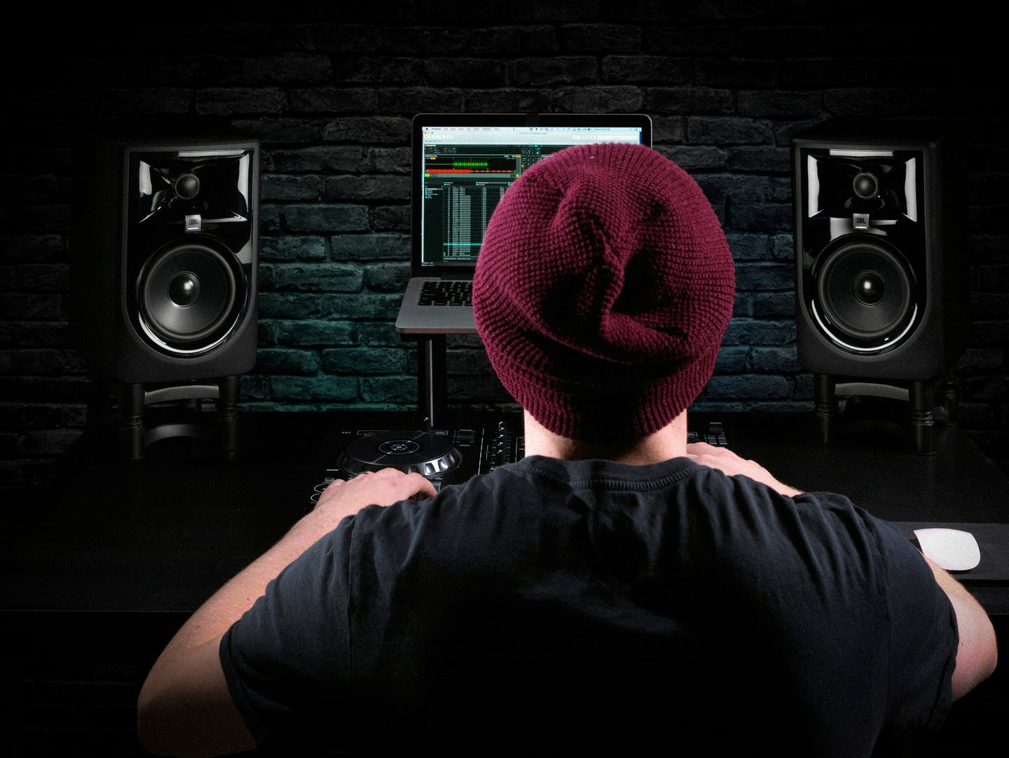 DJ/producer in a home studio with JBL monitors