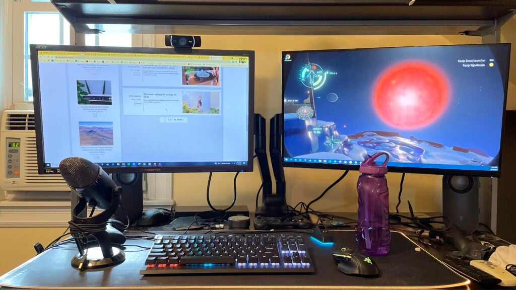 Two gaming monitors, a microphone, gaming keyboard, and an XXL mouse pad in front of a wall.