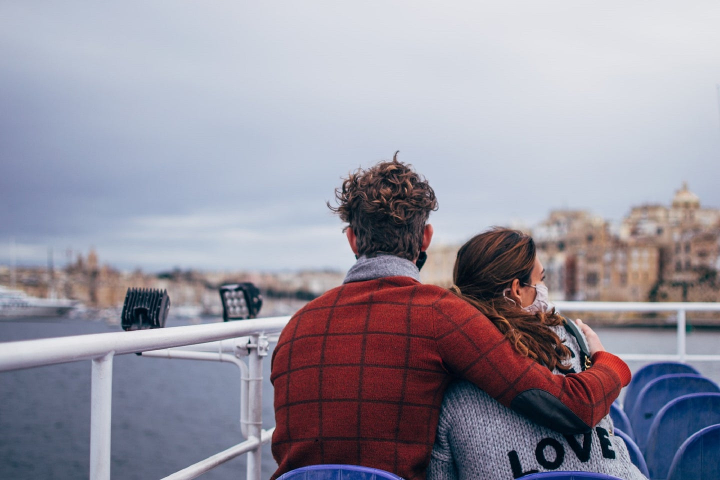 Couple in COVID-19 masks hugging on boat