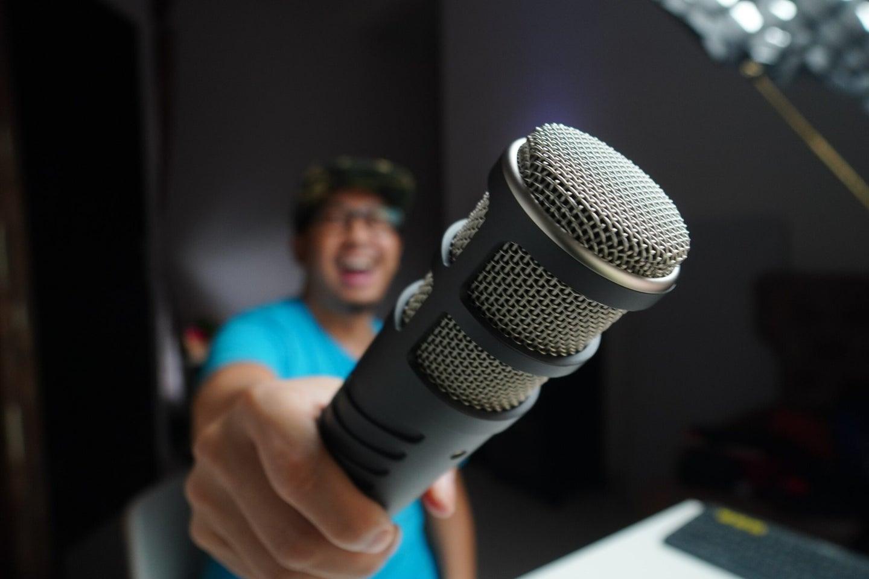 Smiling man holding microphone toward camera