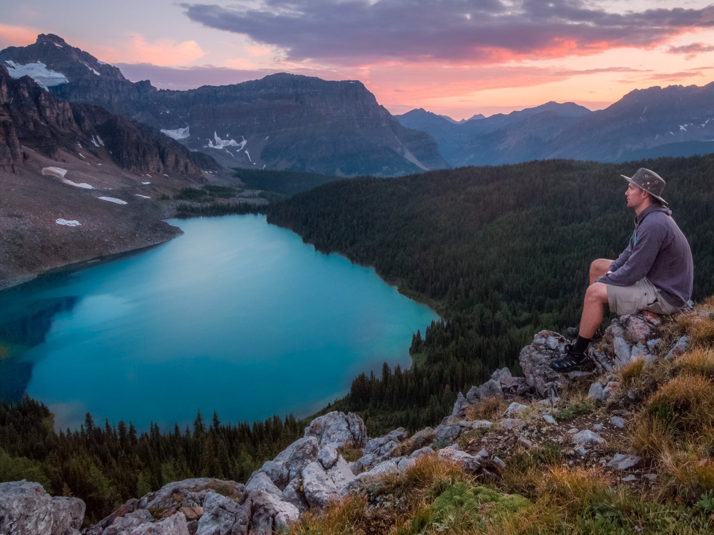 A person wearing a wide-brimmed hat sitting on some rocks high above a bright blue glacial lake in the mountians.