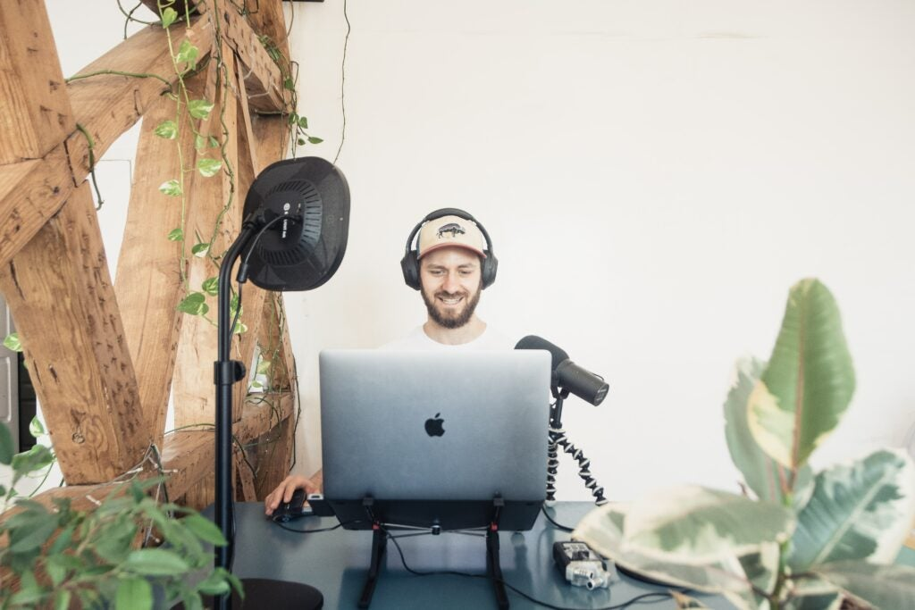 Man at laptop with a Shure SM7B mic in home recording studio