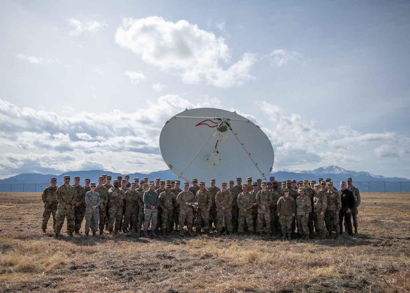 troops stand in front of a satellite dish