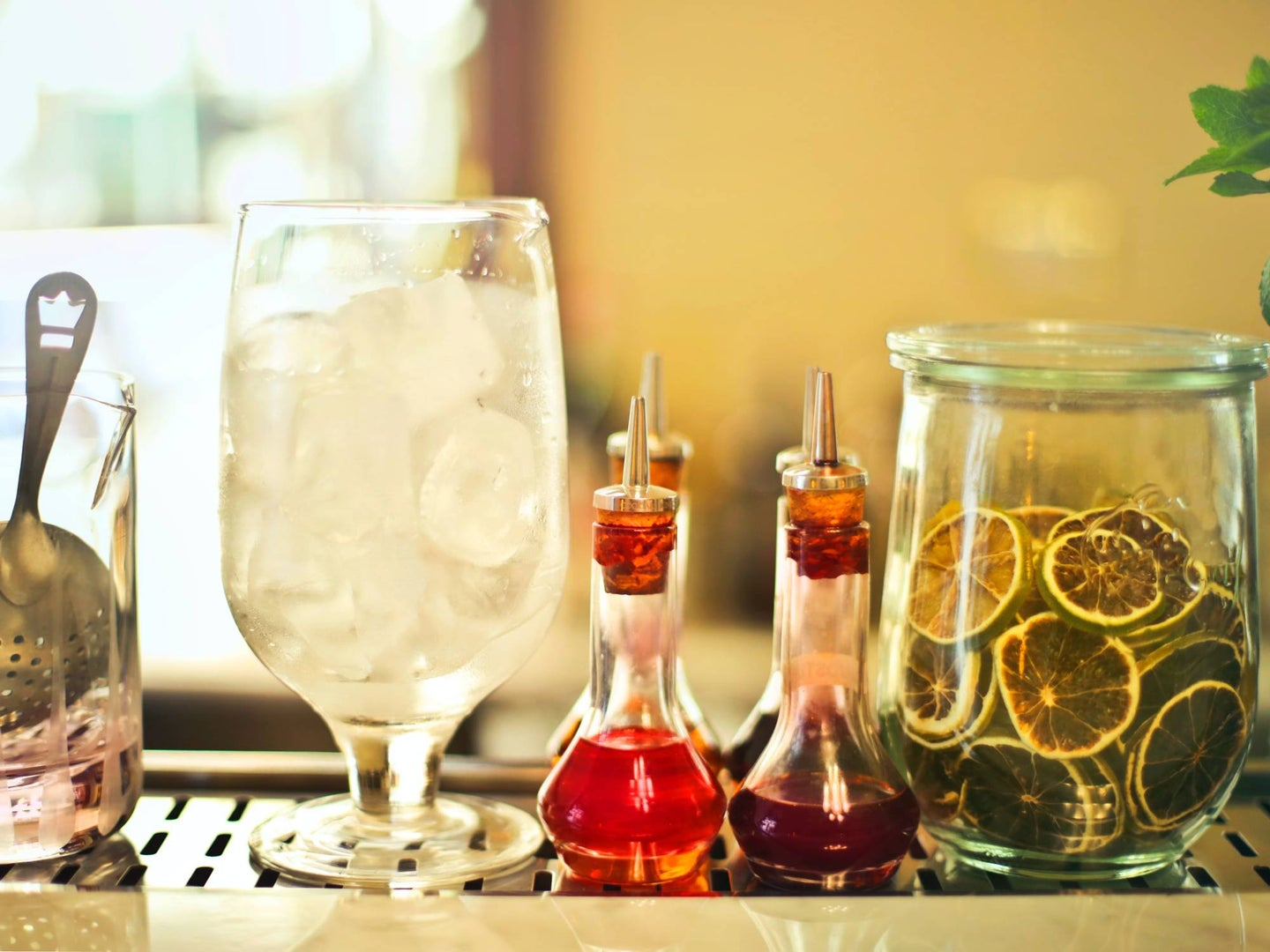 A bar cart with lined-up bottles of infused syrup.