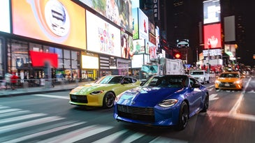 A yellow and blue 2023 Nissan Z driving in Times Square.