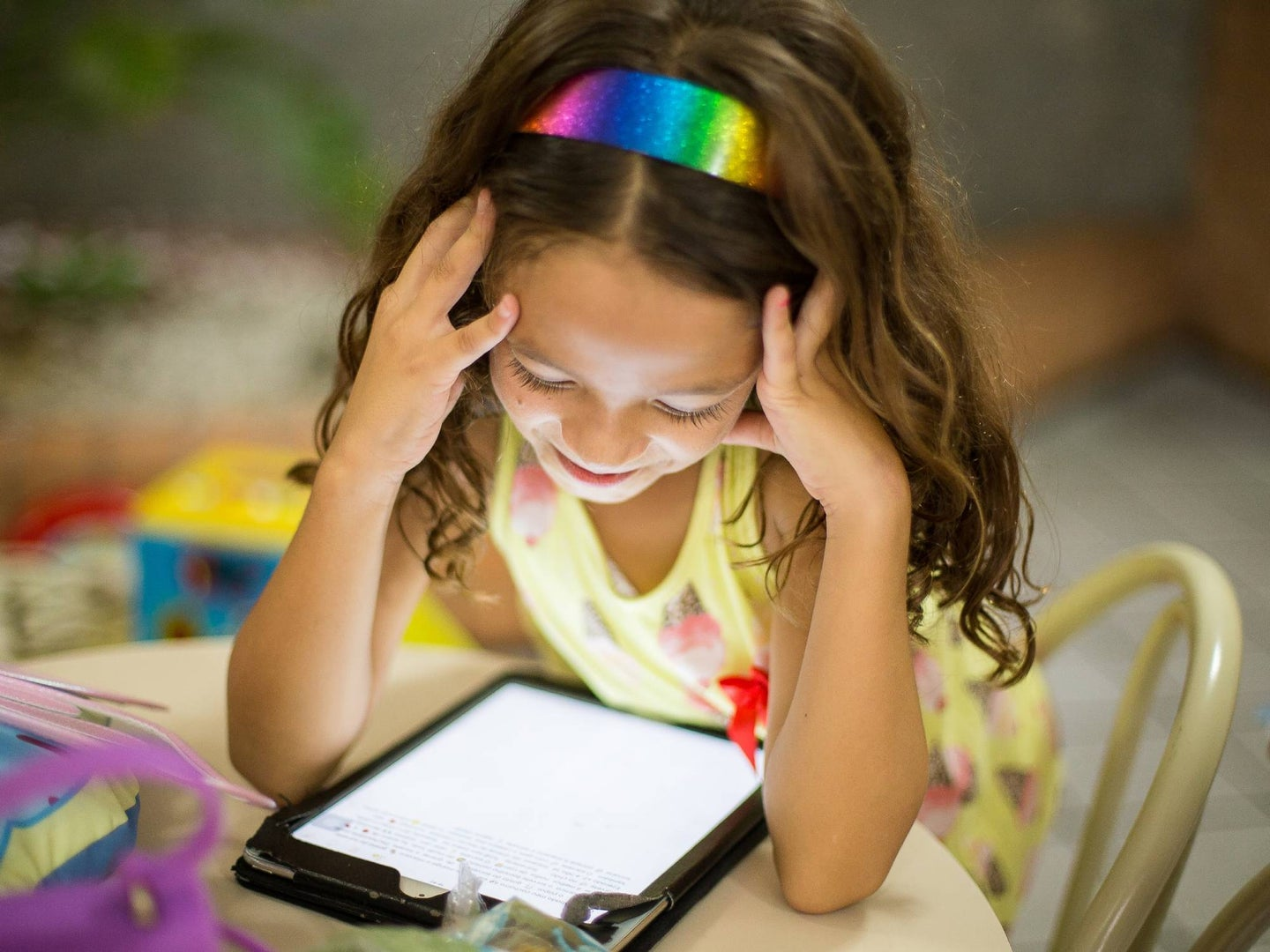 Young child sitting at a table looking at a tablet