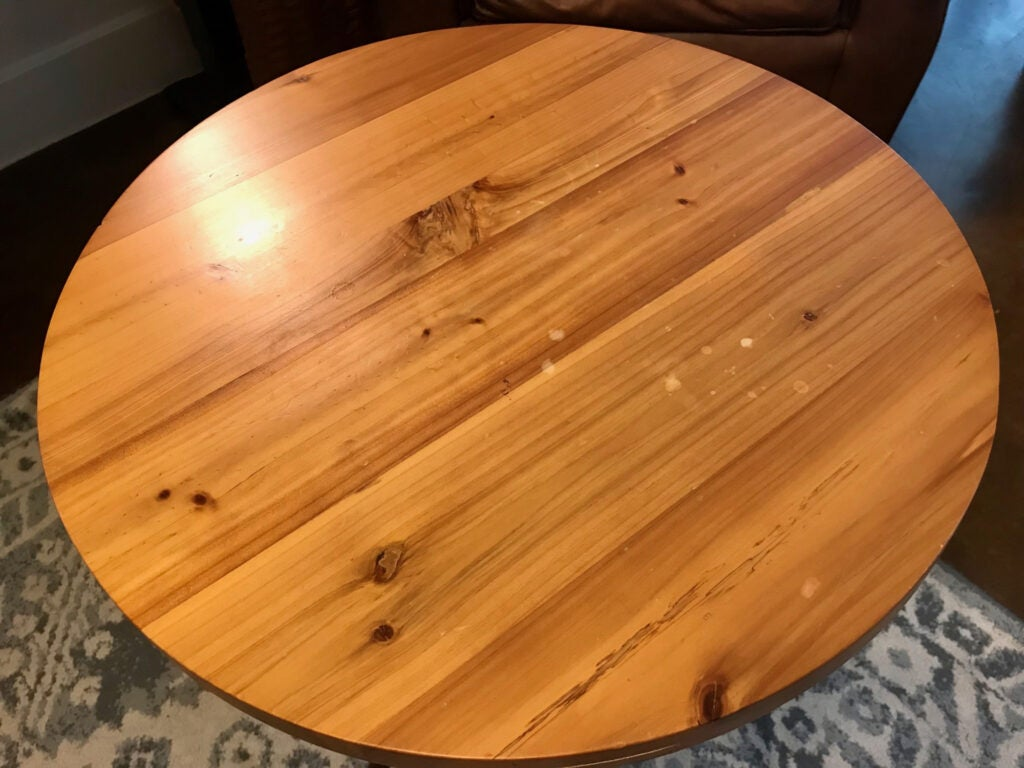 A wooden table with a light finish and some stains.