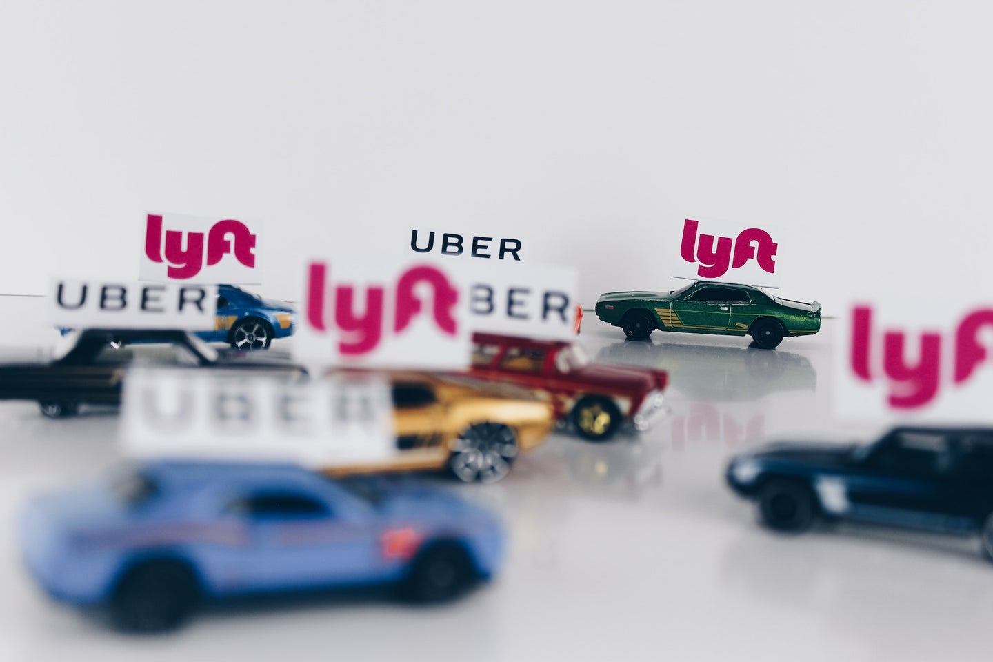 Uber and Lyft signs on tiny cars.