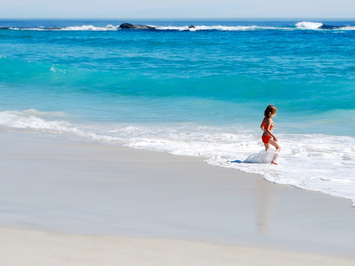 A young child standing alone at the edge of a bright blue ocean, playing in the foam.