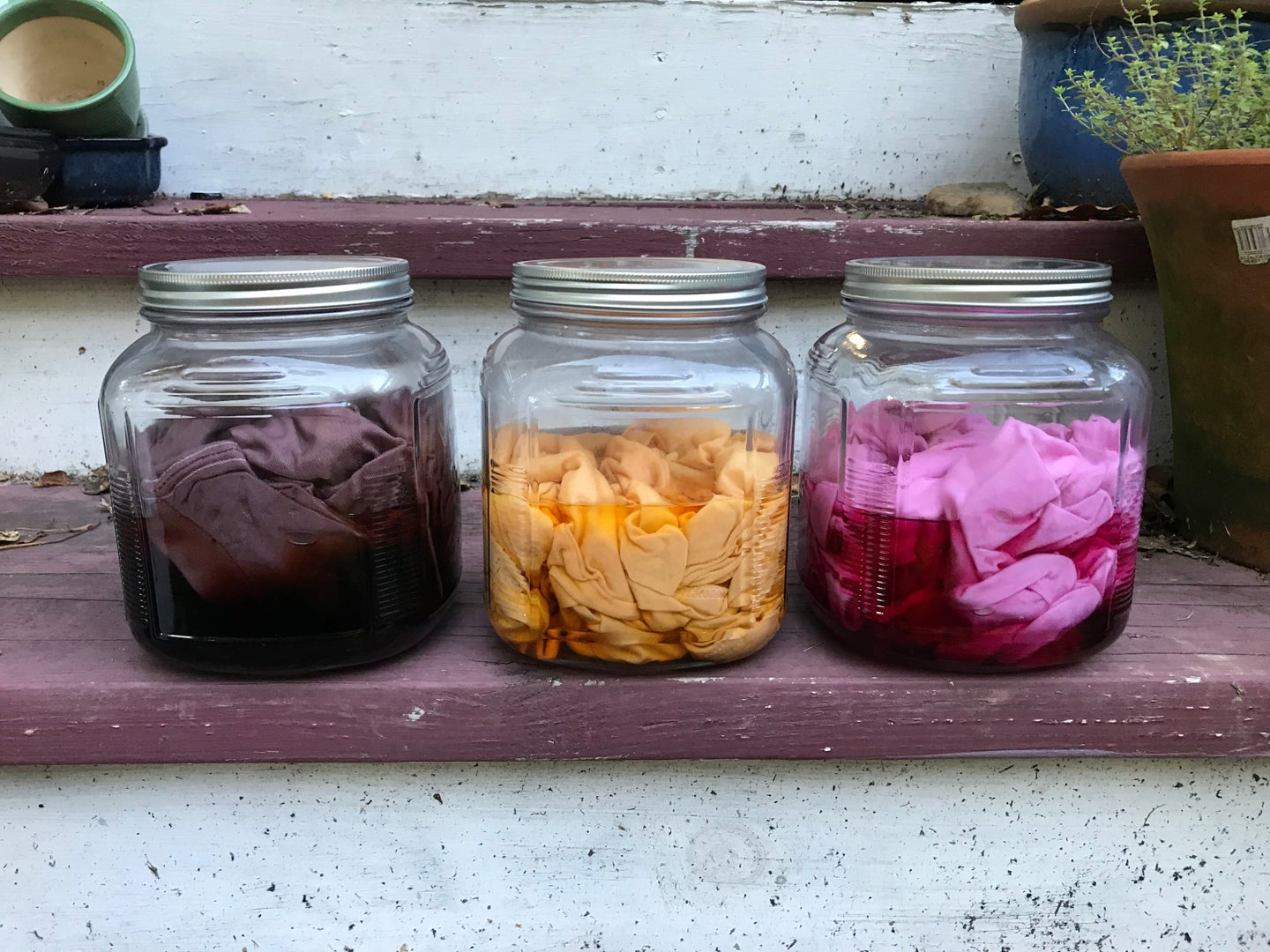 Three mason jars with homemade fabric dye and some dyed shirts inside them. From left to right: purple, orange, and pink.