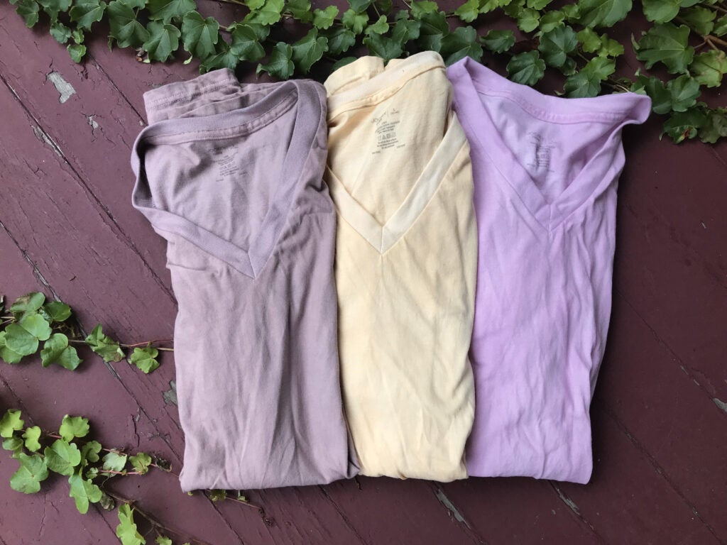 Three DIY dyed shirts on a wooden stair. From left to right: gray, yellow, and pink.