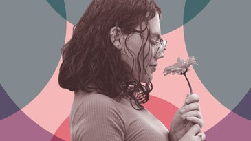 A person with glasses and curly, shoulder-length hair holding a flower and smelling it with their eyes closed.