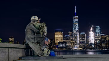 a statue of a firefighter sits with the One World Trade Center tower in the background