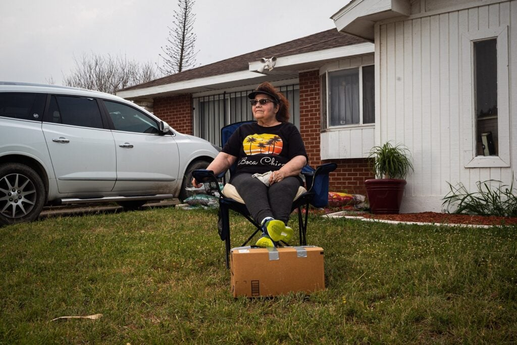 Boca Chica, Texas, resident sitting in front of her house