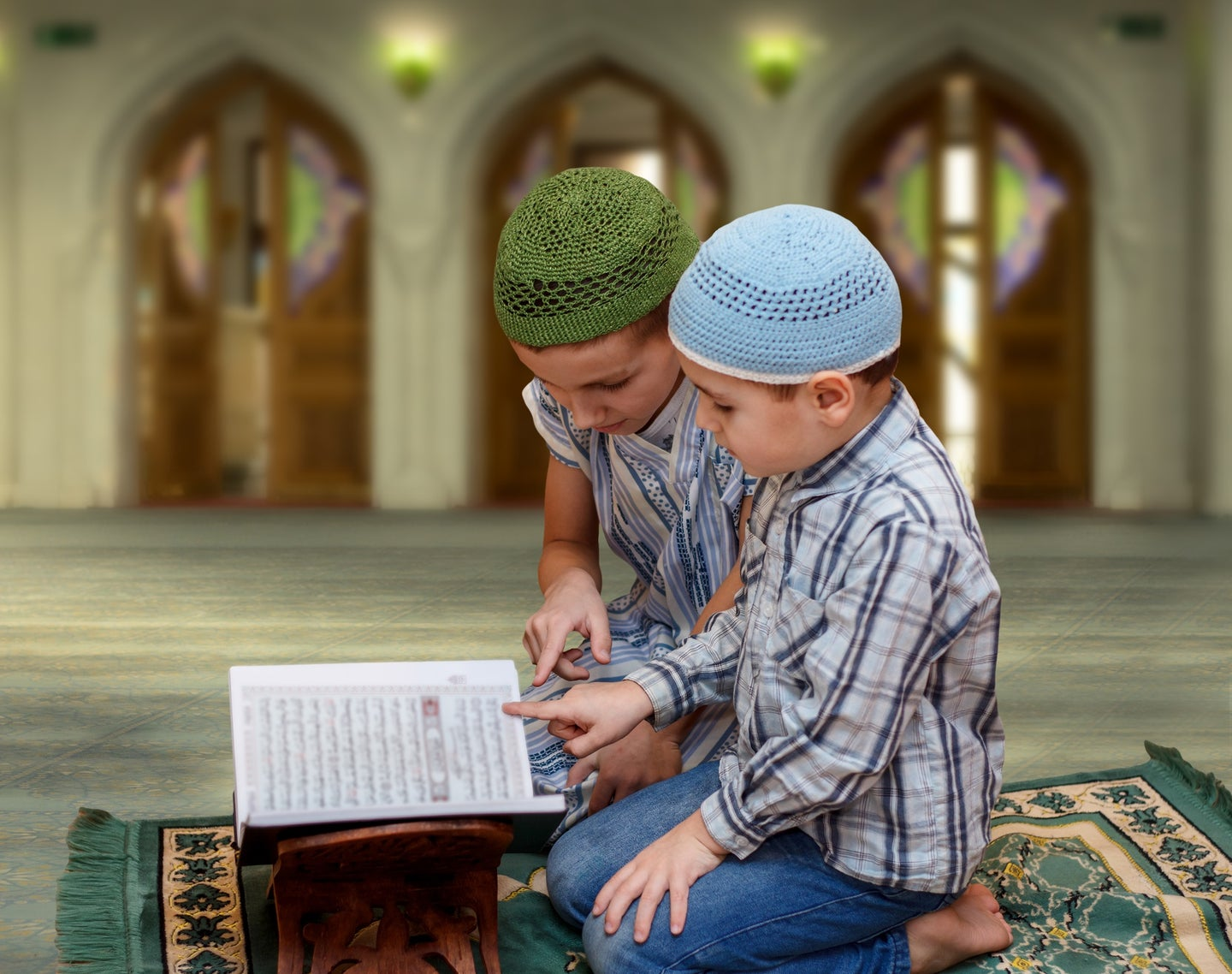 Muslim family reading Quran in mosque