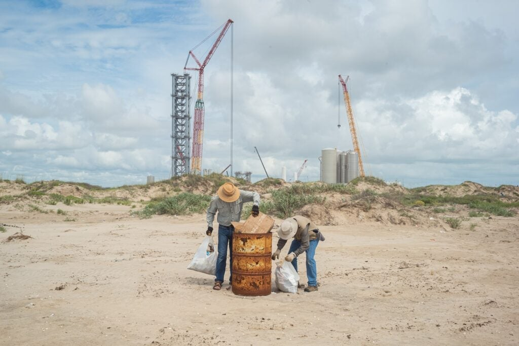 Boca Chica beach cleanup with SpaceX construction in background