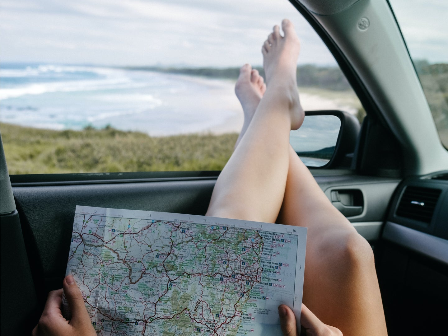 A person sitting in a car with their bare feet out the open window, looking at a road map while overlooking an ocean.