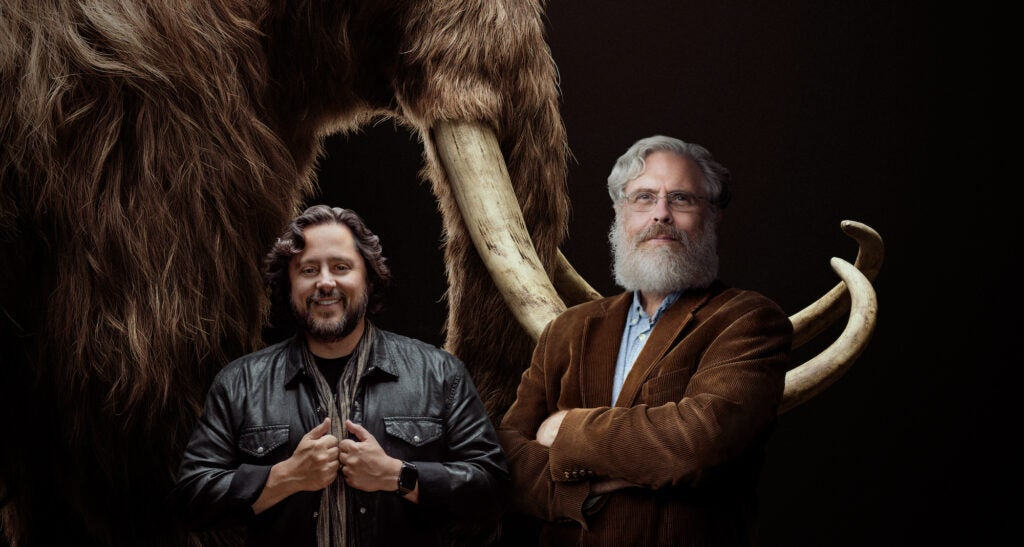 Ben Lamm and George Church in front of a woolly mammoth specimen