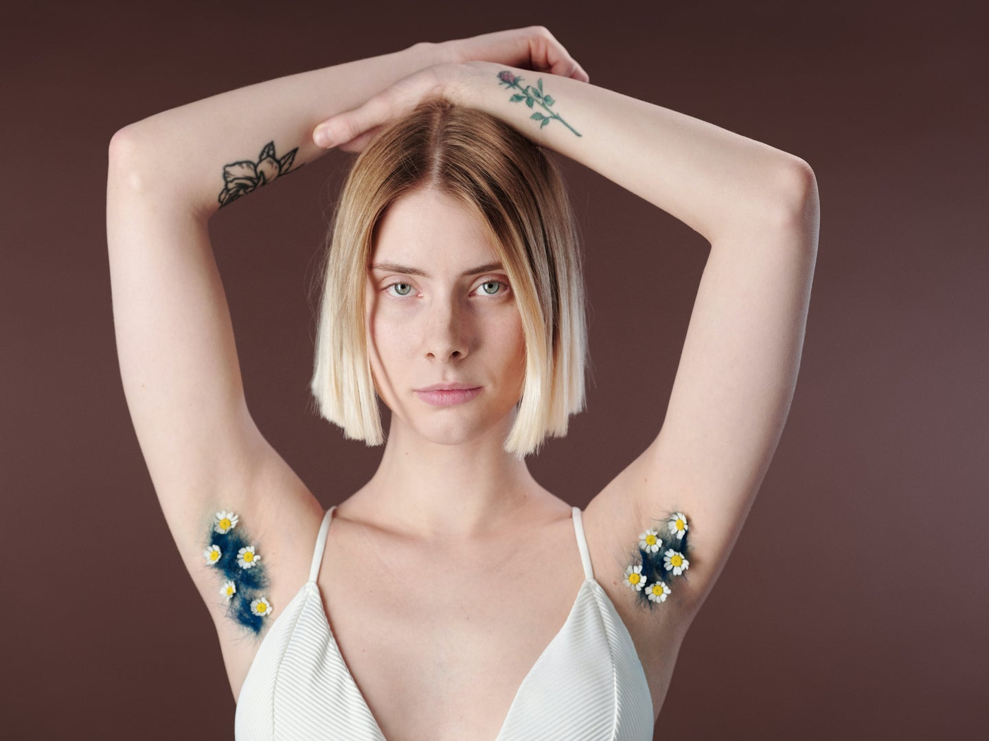A blonde woman in a white top with her arms above her head and flowers in her armpits.