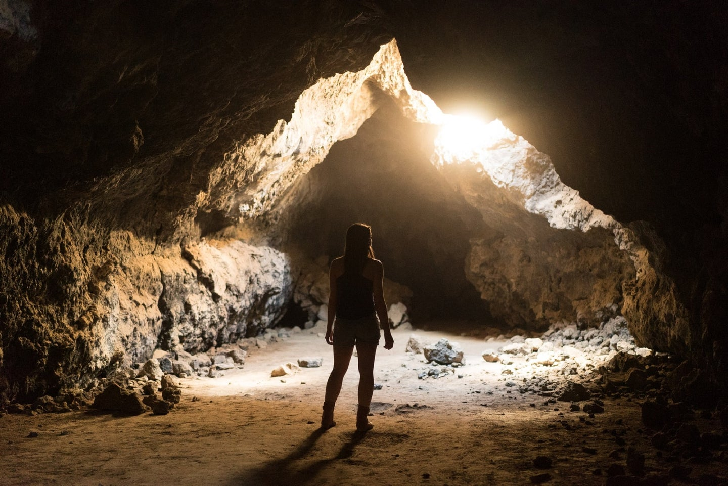 Person with long hair looking at sun through cave