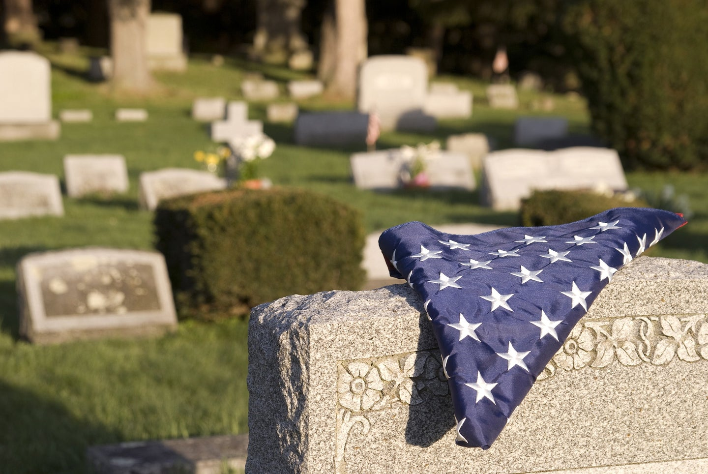 A folded American flag rests on top of a grave stone, with other gravestones in the background.