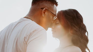 a man and a woman lean in to kiss