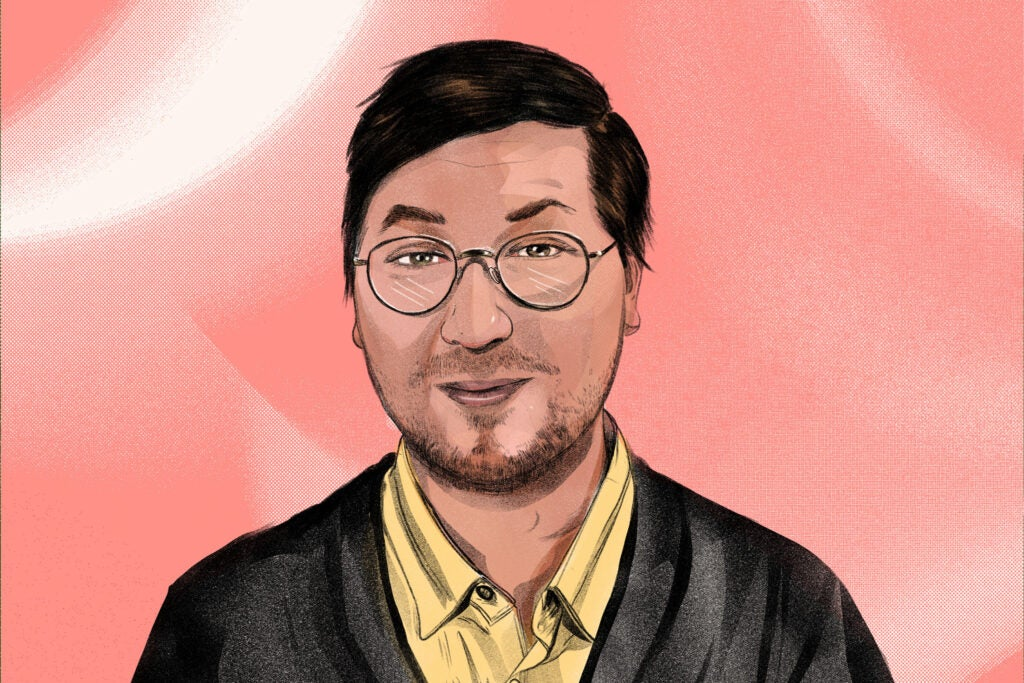 a man with glasses on a pink background