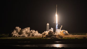 A bright rocket launches against a dark night sky.