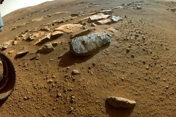 An extremely wide-angle photo of a red, dusty surface, with a grey rock with two holes drilled into it.