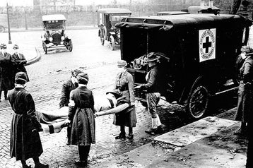 A black and white photo of 1918, nurses load a patient into an ambulance.