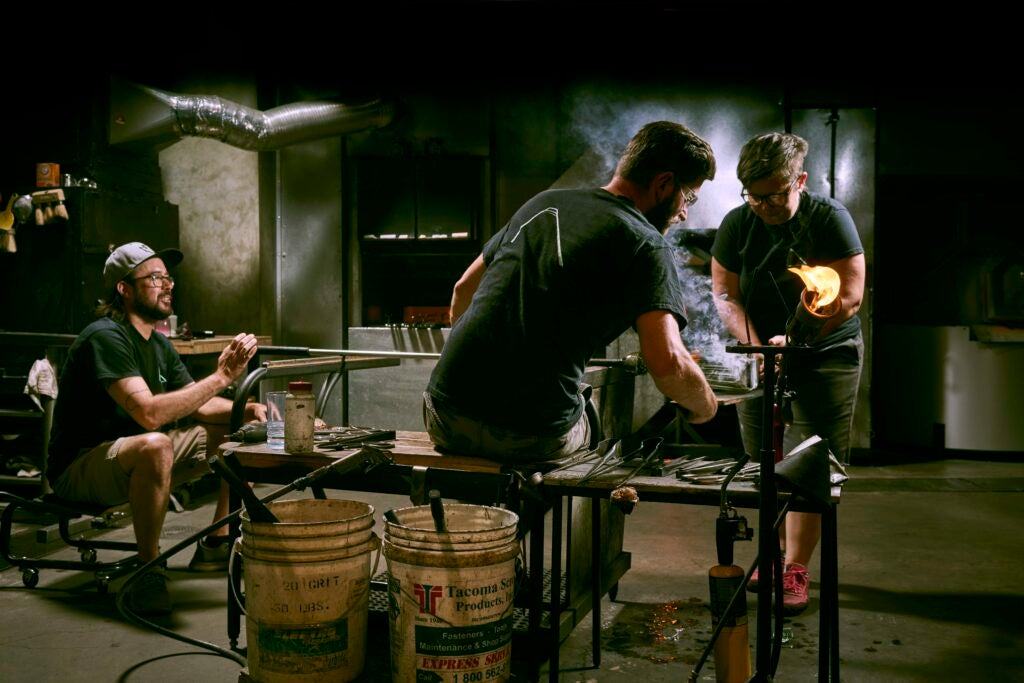 three humans blowing glass together