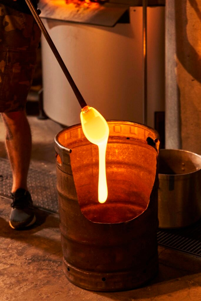 A bucket full of molten glass with a rod dripping some orange liquid glass