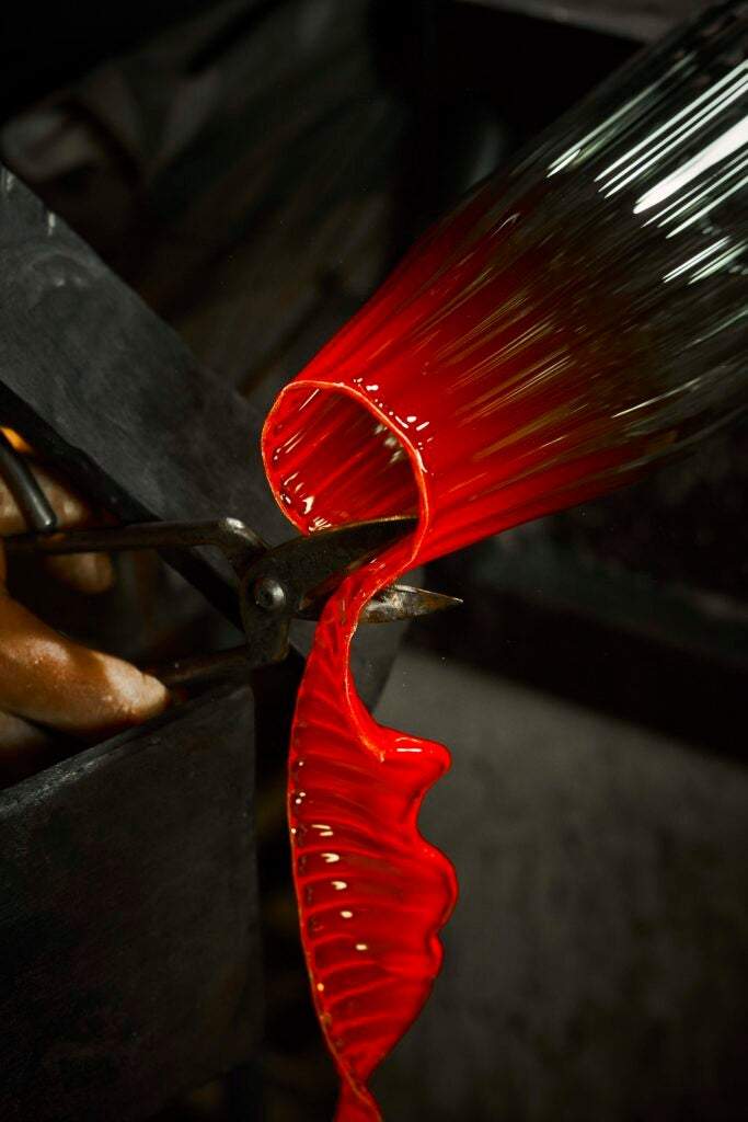 the mouth of a ribbed glass vessel that is red-hot, which someone is cutting with scissors to create a trailing ribbon of molten glass