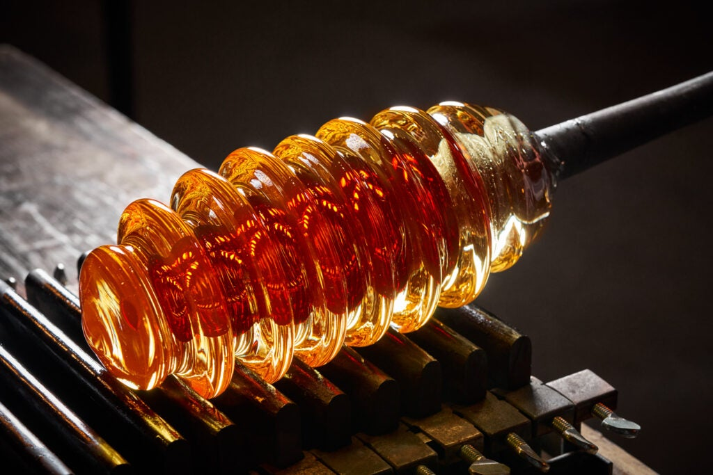 a honeycomb-shaped piece of orange glass sits on top of a metal mold