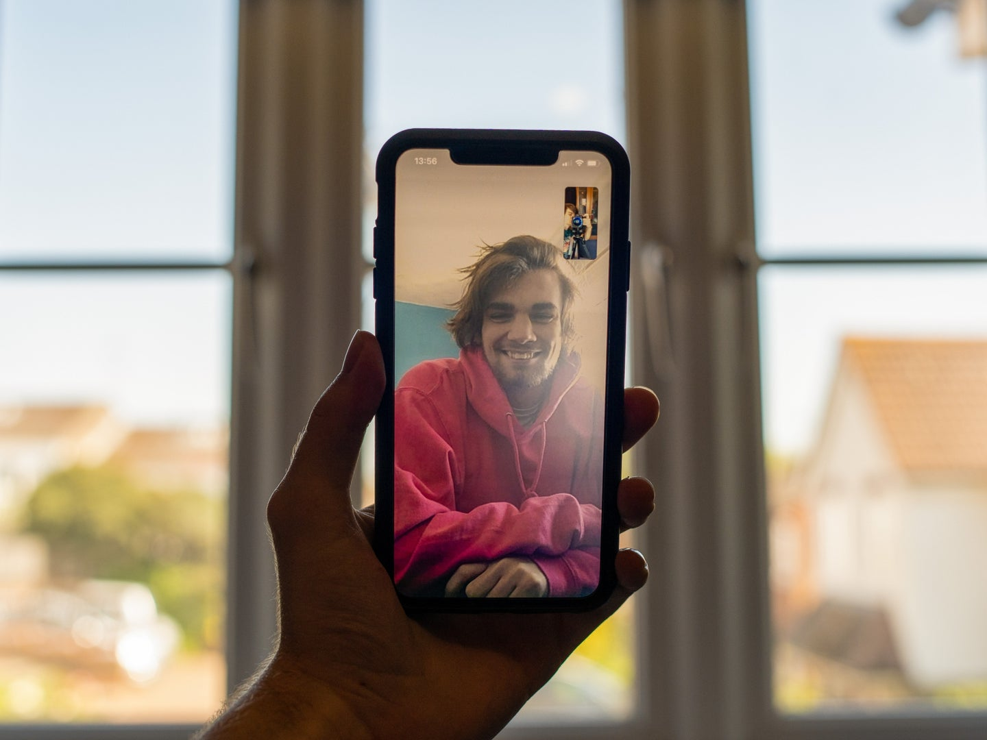 A person holding an iPhone in front of a window while having a FaceTime call with someone in a red sweatshirt.