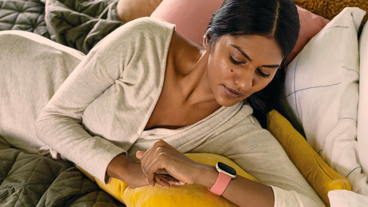 A woman in bed wearing a white long-sleeved shirt, looking at a pink Fitbit on her wrist.