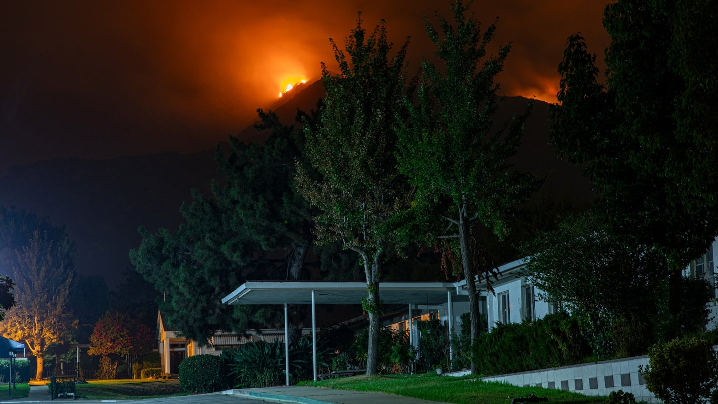 A large home in California being threatened by a wildfire on a distant mountain at night.