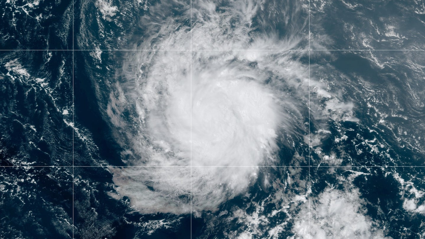 A satellite image of a hurricane, which appears as a white swirling vortex over dark blue water.