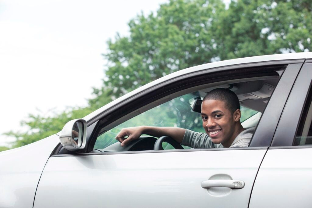 Black teen smiling in the driver's seat of a silver car