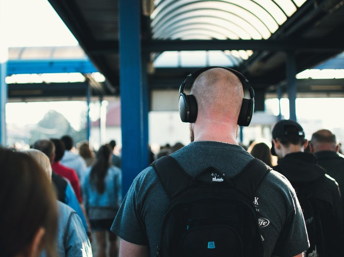 A bald man wearing headphones and a backpack in a crowded area, maybe a train station.