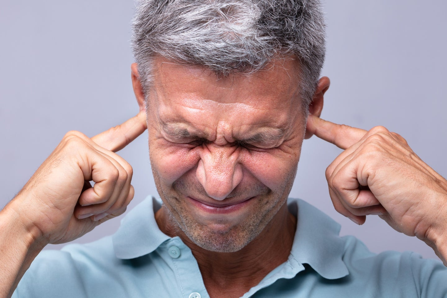 Havana syndrome sufferer holding ears and temple in pain