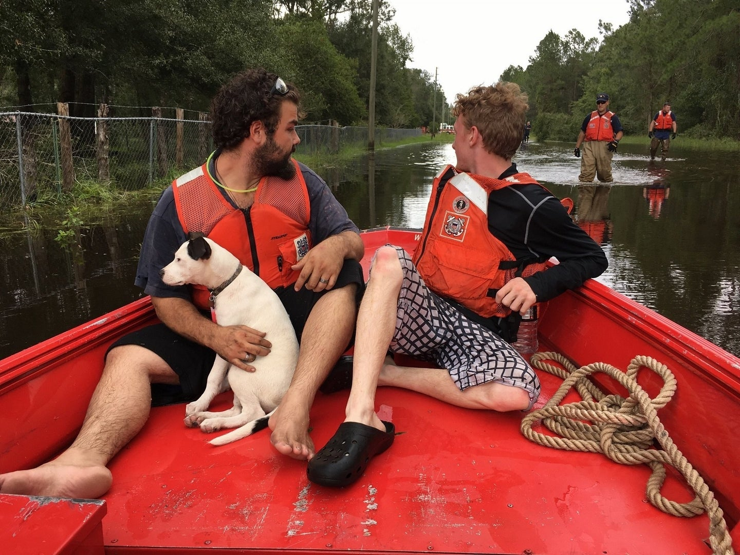 Natural disaster evacuation with two people in life vests on a red boat with a dog