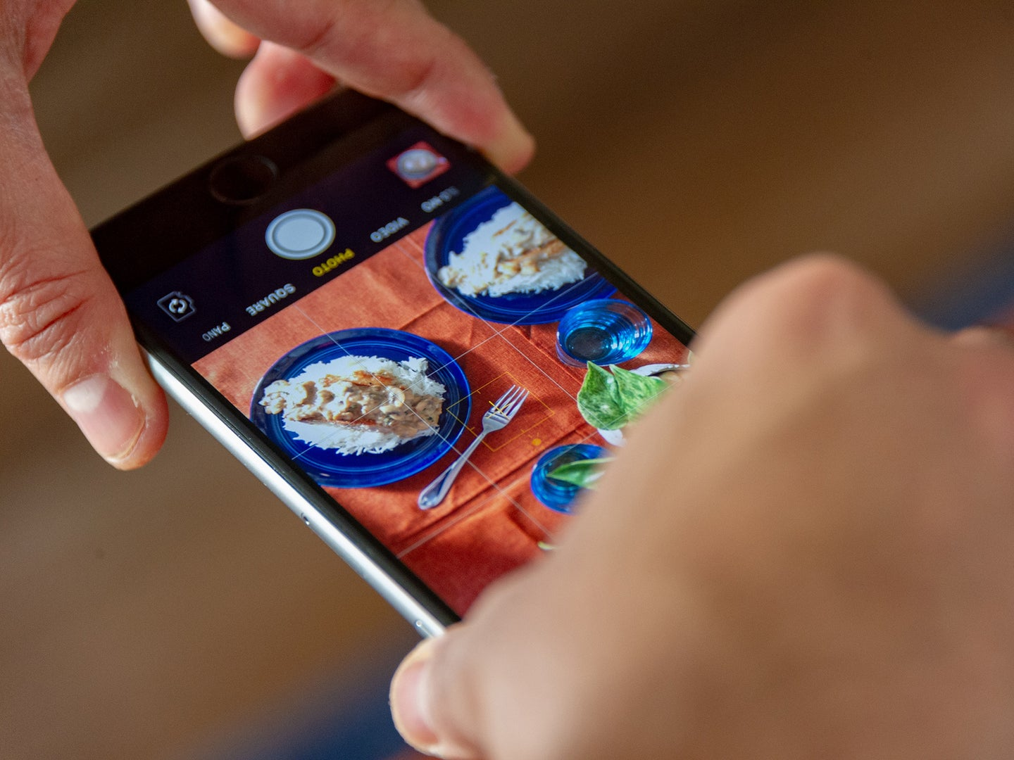 A person using their iPhone to take a photo of some food on a table.