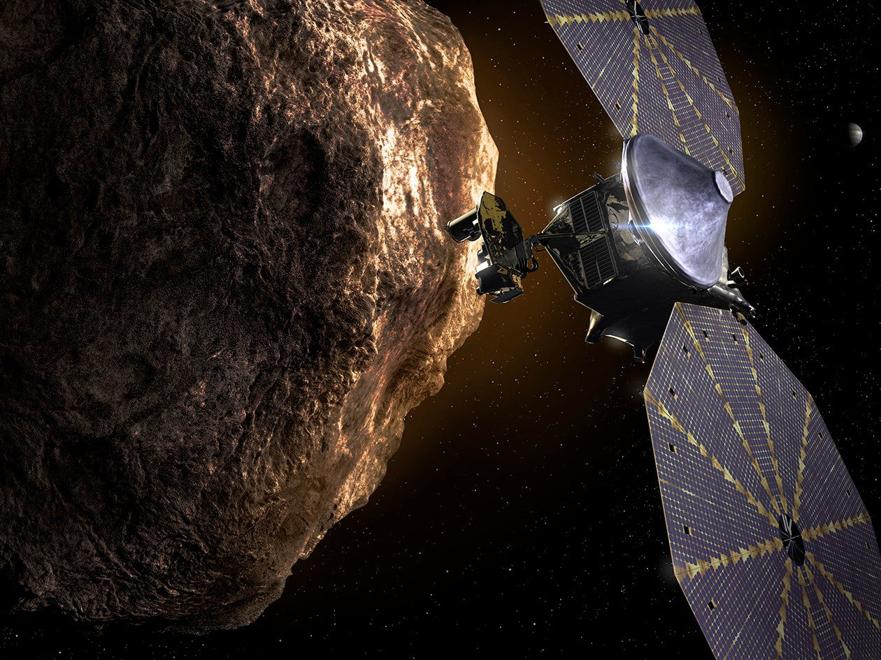 A rocky asteroid takes up the left half of the frame, and a satellite with two large solar panels sits to the right.